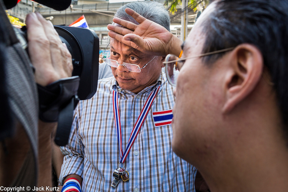 "15 JANUARY 2014 - BANGKOK, THAILAND:  SUTHEP THAUGSUBAN, former Deputy Prime Minister of Thailand and leader of the Shutdown Bangkok anti-government protests, wipes his brow while he gives an interview to a TV network during a protest march. Tens of thousands of Thai anti-government protestors continued to block the streets of Bangkok Wednesday to shut down the Thai capitol. The protest, ""Shutdown Bangkok,"" is expected to last at least a week. Shutdown Bangkok is organized by People's Democratic Reform Committee (PRDC). It's a continuation of protests that started in early November. There have been shootings almost every night at different protests sites around Bangkok. The malls in Bangkok are still open but many other businesses are closed and mass transit is swamped with both protestors and people who had to use mass transit because the roads were blocked.   PHOTO BY JACK KURTZ"