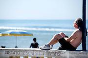 2013/06/23 Roma, prima domenica di estate a Ostia, il mare della capitale. Nella foto un uomo prende il sole sulla rotonda.<br /> Rome, first summer sunday at Ostia, the capital beach. In the picture a man sunbathing on roundabout - &copy; PIERPAOLO SCAVUZZO