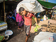 10 NOVEMBER 2014 - SITTWE, MYANMAR: A laborer carries a sack of produce through the market in Sittwe, Myanmar. Sittwe is a small town in the Myanmar state of Rakhine, on the Bay of Bengal.    PHOTO BY JACK KURTZ