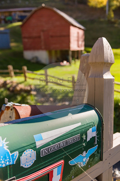 A mail box with In God We Trust by an old wooden barn along the Quilt Trails in Prices Creek, North Carolina. The quilt trails honor handmade quilt designs of the rural Appalachian region.