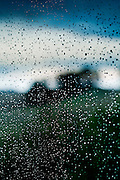 raindrops on window in rural setting