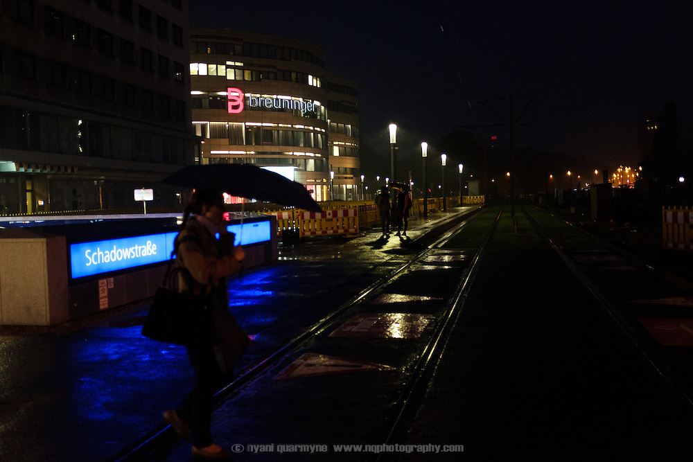 A woman with an umbrella walking past the entrance to the Schadowstraße underground station on a rainy night in central Düsseldorf, Germany on 1 June 2016.