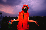 Person wearing a gas mask holding a bottle of sprite Creamfields 2000