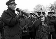 A policeman using a megaphone, while a demonstrator makes fun of him, Criminal Justice Rally, Hyde Park, London UK 1994