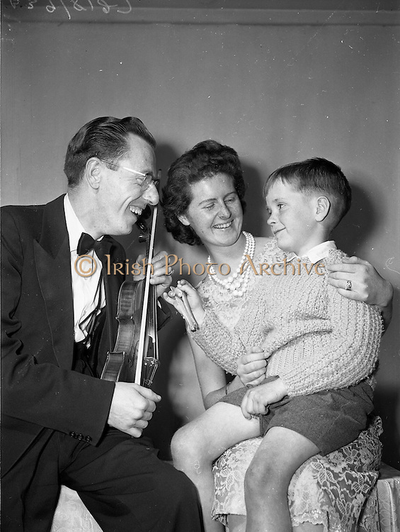 15/05/1959<br /> 05/15/1959<br /> 15 May 1959<br /> Gael Linn Competition at Listowel, Co. Kerry.Seven year old Padraig Carey, Listowel, a member of the boys bone band, which took part in the covert, entertaining two fellow artistes, Sean Maguire, Traditional Fiddler and Aine Nic Cana, Radio Eireann (R.E.). Singer and Abbey Actress.