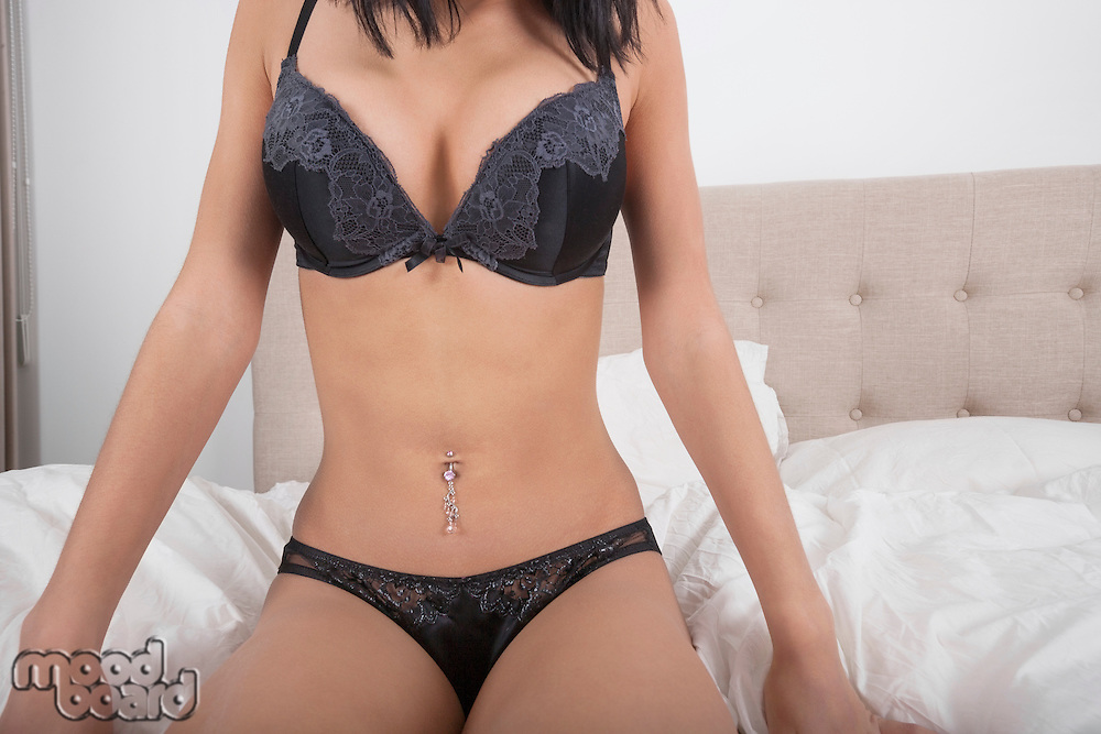 Midsection of woman in lingerie sitting on bed