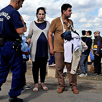Attempting to communicate with the Hungarian police at a reception center a kilometer inside the border from Serbia, Ali and Najibah, Iraqis from Kirkuk,  walked for eight days to get into Hungary.  Najibah was seven months pregnant.  She had had pains in her belly for three days.  She and her husband were taken to a hospital.  Refugees and migrans who have crossed the border from Serbia are being held in a field near Röszke.  The official border reception centres are full and refugees must camp on the ground, dependent on food donated by volunteer groups