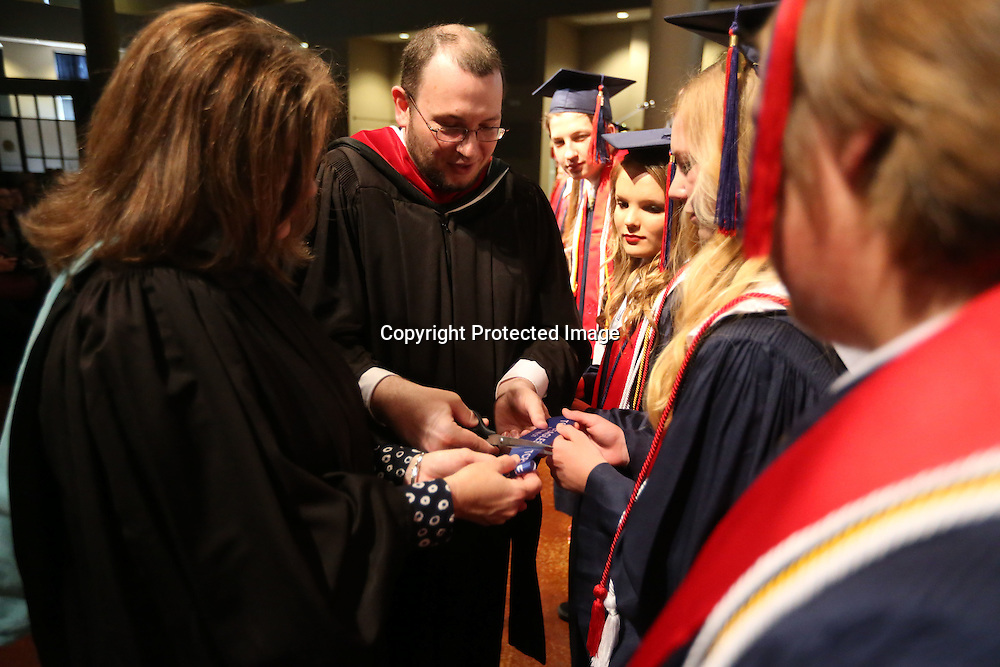 Adam Robison | BUT AT PHOTOS.DJOURNAL.COM<br /> TCPS faculty member James Underwood, center, cuts a piece of ribbon for Salutatorian Claire Golding during the ribbon ceremony at the end of the TCPS graduation ceremony at the Orchard in Tupelo Saturday.