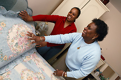 Carer helping elderly woman make the bed,