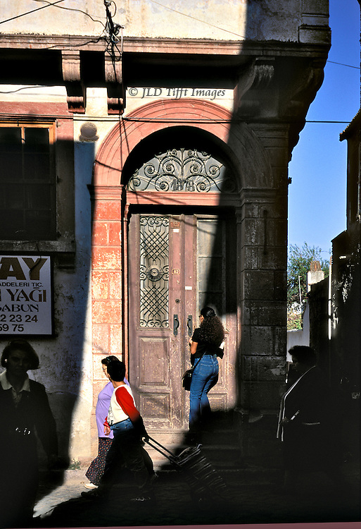 Sharp shadow projected on doorway of an old but still occupied house in Ayvalik.  Date on metal tympanum over the door says 1878.  A young woman in jeans opens the door with a key, while two other women walk by.