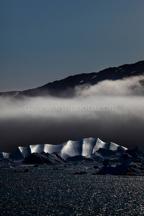 Iceberg under cloud, Kangerdlussuaq Fjord, East Greenland. Taken from the deck of the Greenpeace ship Arctic Sunrise, during a 2009 expedition to investigate the effects of climate change in the Arctic.
