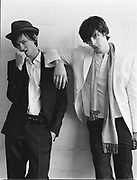 Two young men standing leaning against white wall.