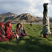 A young boy entertains a group of girls by performing a head stand. The Wakhan Corridor is one of the most remote regions of Afghanistan. Much of it is only reachable on foot or by horse or yak and is inhabited by nomads living in yurts. Sarhad de Broghil, Badakhshan, Afghanistan, August 2009.