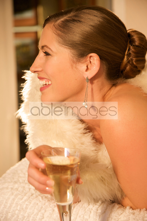 Profile of a woman wrapped in a swan feather stole holding a glass of champagne - close up