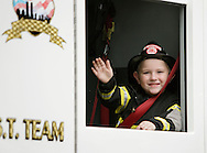 Salisbury Mills, New York - A young boy dressed as a fireman waves from inside a fire truck  during the Orange County Volunteer Firemen's Association (OCVFA) annual parade on Sept. 24, 2011.