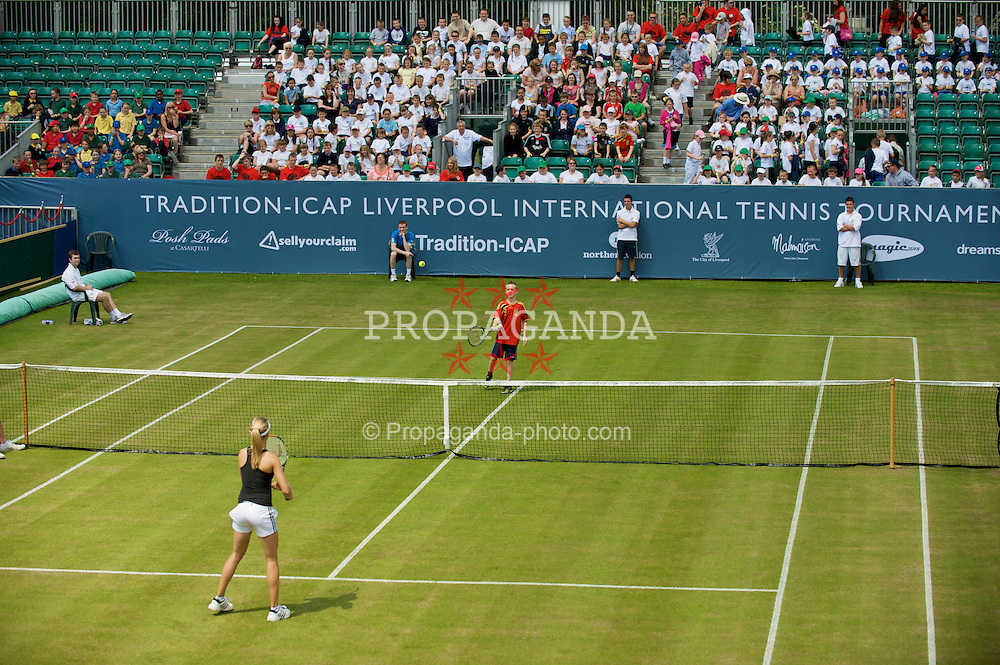 LIVERPOOL, ENGLAND - Tuesday, June 16, 2009: A young fan gets the opportunity to play against Eugenie Bouchard (CAN) during the Tradition ICAP Liverpool International Tennis Tournament 2009 at Calderstones Park. (Pic by David Rawcliffe/Propaganda)