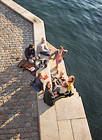 Young people enjoying wine at sunset on the canal in Copenhagen, Denmark.