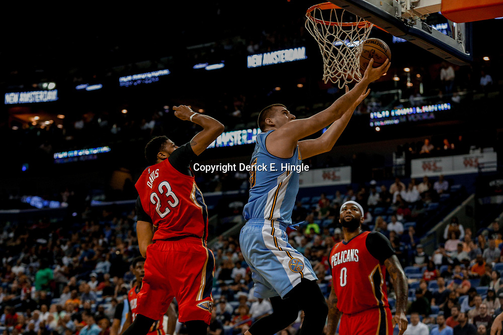 Apr 4, 2017; New Orleans, LA, USA; Denver Nuggets forward Nikola Jokic (15) shoots past New Orleans Pelicans forward Anthony Davis (23) and forward DeMarcus Cousins (0) during the first quarter of a game at the Smoothie King Center. Mandatory Credit: Derick E. Hingle-USA TODAY Sports