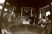 Mar 6, 2006; Tokyo, JPN; Asakusa.A visitors places incense in the large bronze incense bowl in front of the Senso-ji Buddhist temple where visitors come and waft the smoke (considered to be the breath of the gods) upon themselves for its supposed curative powers...Photo credit:  Darrell Miho