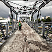 A man walking on bridge that passes above the railroad of Narva, just close to the border between Estonia and Russia