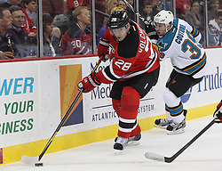 Oct 21; Newark, NJ, USA; New Jersey Devils defenseman Anton Volchenkov (28) skates with the puck past San Jose Sharks center Logan Couture (39) during the first period at the Prudential Center.