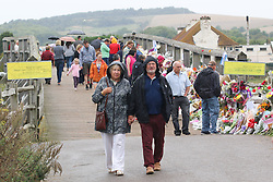 © Licensed to London News Pictures. 29/08/2015. Shoreham, UK.  A stead stream of people wishing to pay their respect keeps arriving at the Toll bridge in Shoreham where thousands of flowers have arrived over the last week  since the plane crash of the Hawker Hunter T7 jet on Saturday August 22nd what killed 11 people. Today a one minute silence was held on the bridge attended by Thousands of people, Today August 29th 2015. Photo credit : Hugo Michiels/LNP