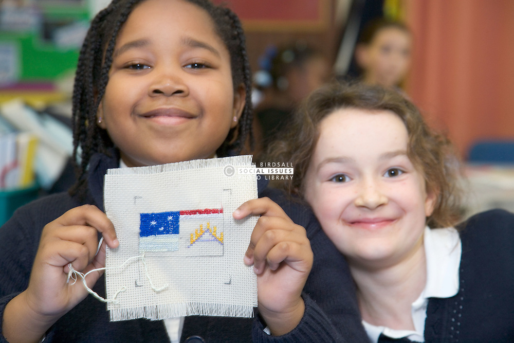Primary school pupil holding up her handiwork during a sewing lesson at school; whilst a friend looks on,