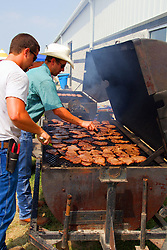 01 August 2014:   McLean County Fair.  Vendors grill hamburgers and pork chops for sandwiches .