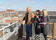 Kelly Bemus (from right) of Skogman Realty points out various buildings downtown to Barb Mochal and Dennis Mochal of Olatha, Kansas while on the roof patio of the Bottleworks Loft Condominiums building, 905 3rd St. SE in Cedar Rapids on Saturday, February 18, 2012. (Stephen Mally/Freelance)