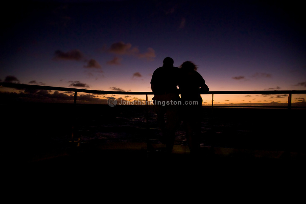 Silhouette of a young adult man and woman on the deck of a cruise ship at sunset on the Atlantic Ocean.