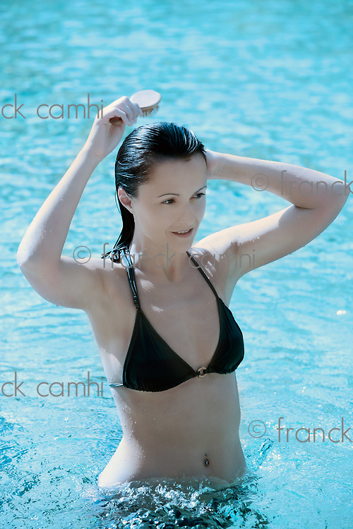 beautiful brunette caucasian relaxing in a swimming pool