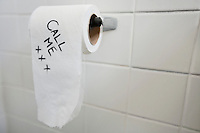 Close-up of toilet paper with text in bathroom