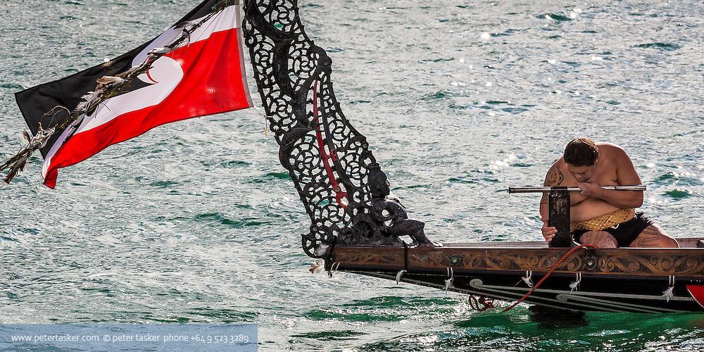 Maori tiller man, waka, and flag.