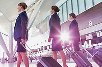 Portrait of young beautiful confident flight attendants walking in airport