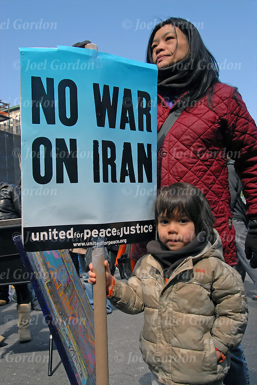 """Mother with her 3 year son holding sign """"NO WAR ON IRAN"""" united for peace and justice. .Join hands symbolize unity in the call for peace in River to River Join Hands For Peace on 3/22/08. Hands Across 14th Street from 11th Ave to Ave A.  After 5 years of war to bring all the troops home now."""