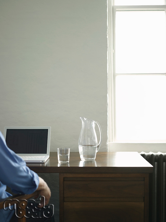Person sitting at desk with laptop and jug of water back view (cropped)