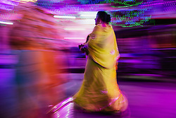 Motion-blur of a woman walking in colorful sari, Jodphur, Rajasthan, India,
