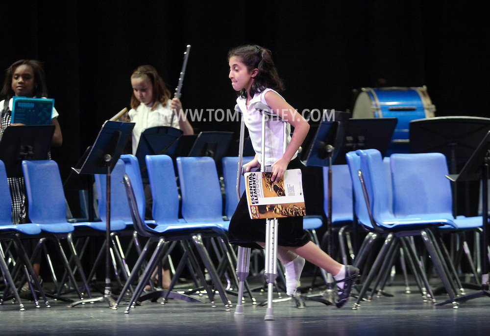 Middletown, NY - A girls with an injured foot uses crutches to leave the stage after performing in an elementary school band concert on the stage at Middletown High School on May 28, 2008.