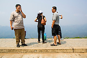 16 MARCH 2013 - ALONG HIGHWAY 13, LAOS:  Chinese tourists at a scenic overlook between Vang Vieng and Luang Prabang, Laos on Highway 13. The paving of Highway 13 from Vientiane to near the Chinese border has changed the way of life in rural Laos. Villagers near Luang Prabang used to have to take unreliable boats that took three hours round trip to get from the homes to the tourist center of Luang Prabang, now they take a 40 minute round trip bus ride. North of Luang Prabang, paving the highway has been an opportunity for China to use Laos as a transshipping point. Chinese merchandise now goes through Laos to Thailand where it's put on Thai trains and taken to the deep water port east of Bangkok. The Chinese have also expanded their economic empire into Laos. Chinese hotels and businesses are common in northern Laos and in some cities, like Oudomxay, are now up to 40% percent. As the roads are paved, more people move away from their traditional homes in the mountains of Laos and crowd the side of the road living off tourists' and truck drivers.   PHOTO BY JACK KURTZ