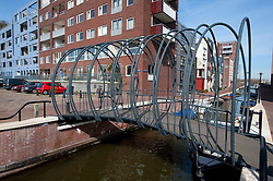 modern steel footbridge over canal in new Java Island housing development in Amsterdam The Netherlands