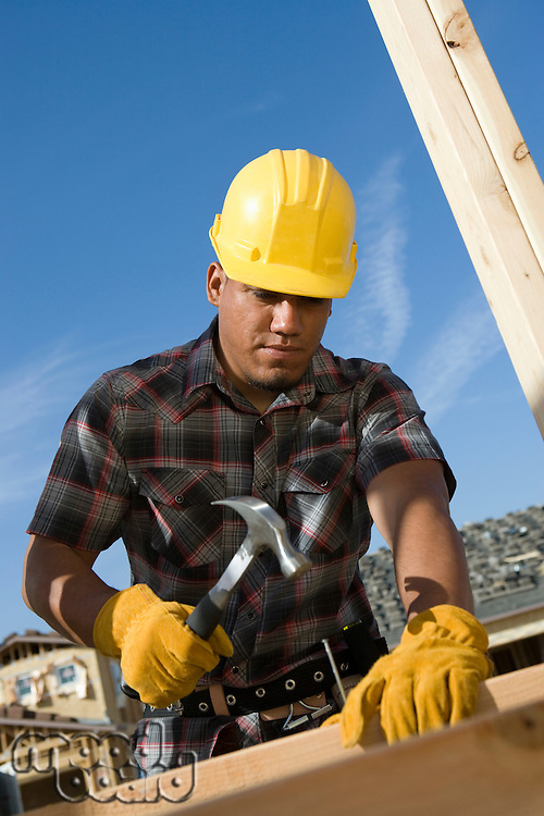 Construction worker hammering nail on construction site