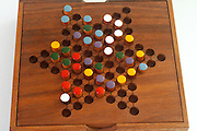 Chinese checkers colour pegs on a wooden board