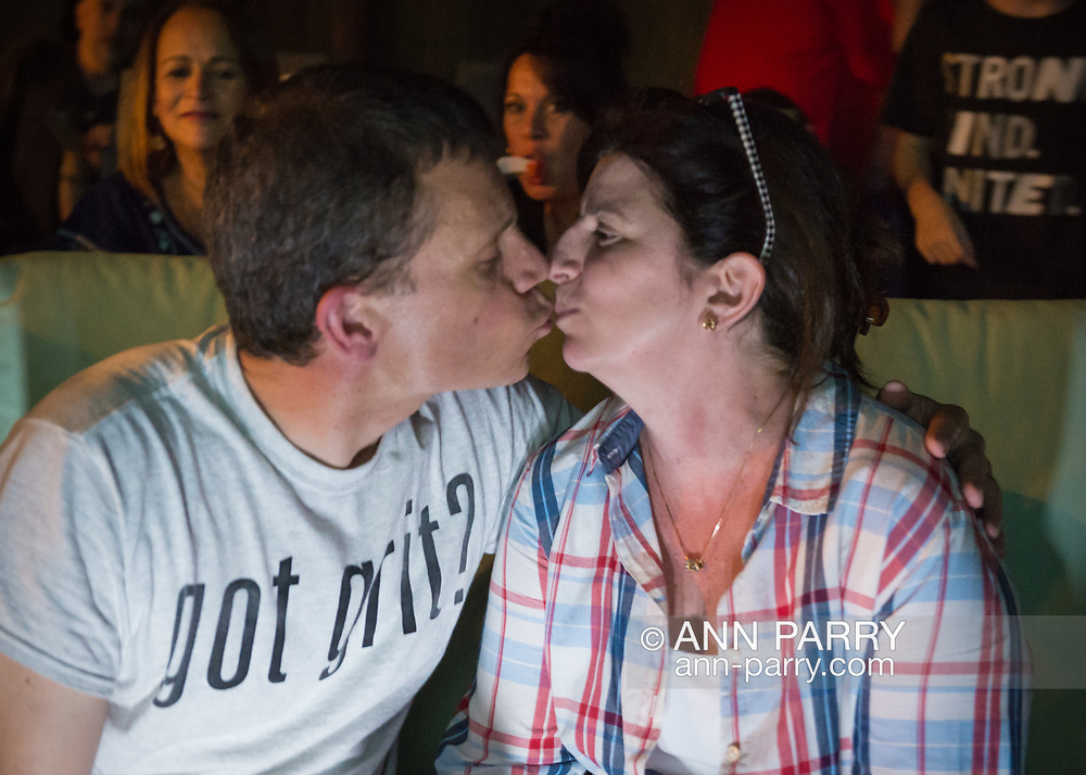 """Merrick, New York, USA. 11th June 2017.  """"American Grit"""" TV contestant CHRIS EDOM, 48, (wearing GOT GRIT? T-shirt) and his wife JOAN EDOM, both of Merrick, kiss each other as they host backyard Viewing Party for Season 2 premiere. Show. Edom family and neighbors watched Episode 1 of FOX network reality television series that Sunday night outdoors."""