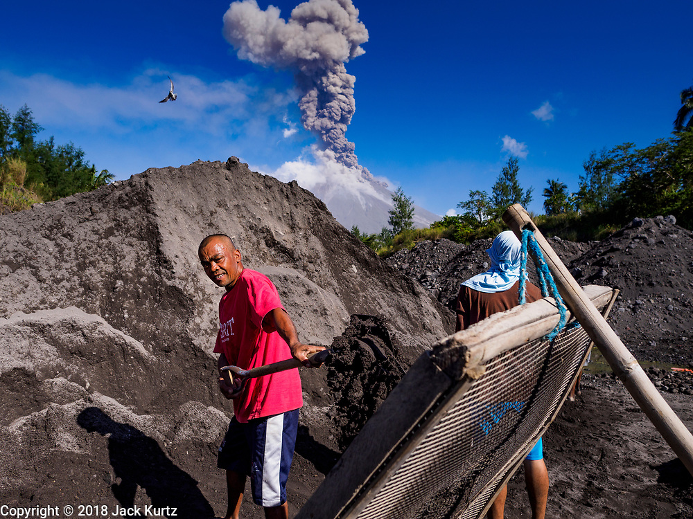 23 JANUARY 2018 - DARAGA, ALBAY, PHILIPPINES: Sand and gravel miners work in a riverbed of volcanic soil while the Mayon volcano erupts Tuesday. The Mayon volcano continued to erupt Tuesday, although it was not as active as it was Monday. There were ash falls in communities near the volcano. This is the most active the volcano has been since 2009. Schools in the vicinity of the volcano have been closed and people living in areas affected by ash falls are encouraged to stay indoors, wear a mask and not participate in strenuous activities.    PHOTO BY JACK KURTZ