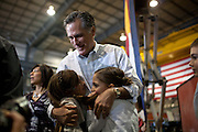 GOP presidential candidate Mitt Romney hugs two of his granddaughters backstage at a campaign rally in Colorado Springs, Colorado, February 4, 2012.