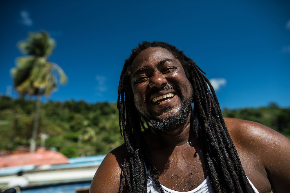 "MARACAS BAY, TRINIDAD - FEBRUARY 14, 2017: Adrian Baptiste, 38, laughs on the beach. Mr. Baptiste hunts the hammerhead sharks that are served in the ""shark n' bake"" sandwiches that are sold at a number of seaside food stands at Maracas Bay, the most popular beach within reach of the capital where crowds of people flock to go swimming in the clean, warm sea backed by lush green hills.  PHOTO: Meridith Kohut for The New York Times"
