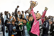 Sporting Kansas City's Paulo Nagamura, front left, and goalkeeper Jimmy Nielsen, front right, hold the MLS Cup as they celebrate their 2-1 win over Real Salt Lake in the MLS Cup final soccer match in Kansas City, Kan., Saturday, Dec. 7, 2013. (AP Photo/Colin E. Braley)