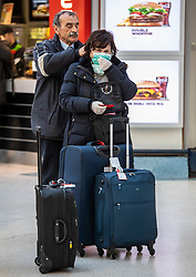 © Licensed to London News Pictures. 02/03/2020. London, UK. A man helps his fellow traveller with her masks as they arrive on the Gatwick Express at Victoria Station with one of them in a protective mask and rubber gloves as fears of a pandemic increase after 4 new cases of Coronavirus are confirmed in the UK. Photo credit: Alex Lentati/LNP