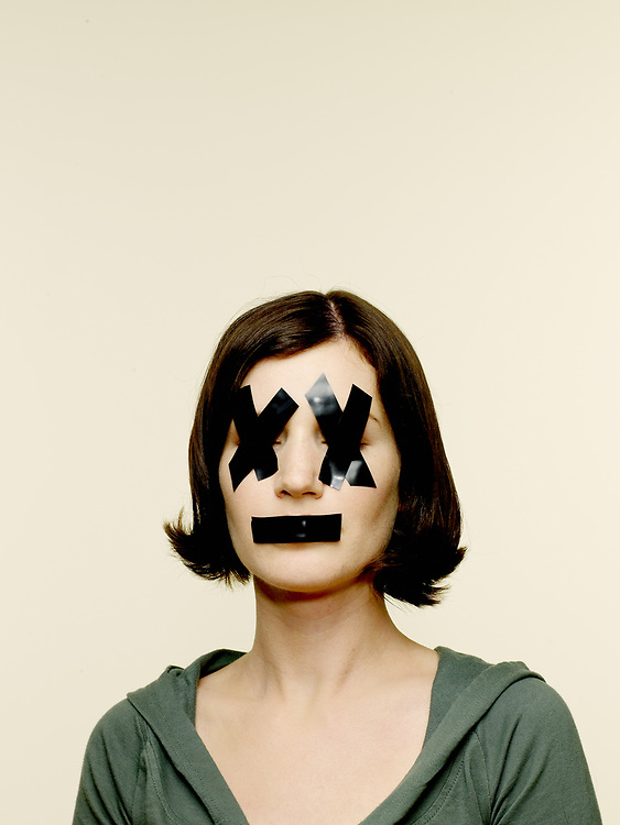 Portrait of woman with black electrical tape over eyes and mouth.