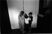 Young ringbearers peek through the church door, waiting for their cue during a wedding rehearsal.